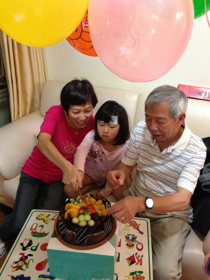 Cutting the cake with her grandparents