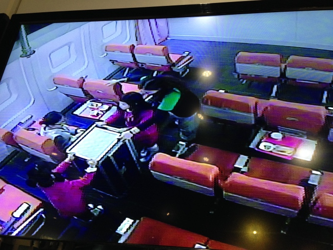 "We were only allowed to watch from a screen outside the plane. This is a photo of Brianne and Bridgette serving the ""passengers"" inside the cabin."